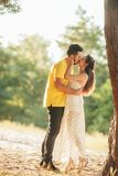Young enamored couple kisses in forest. Young enamored couple kisses in forest against background of tree royalty free stock photo