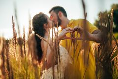 Young enamored couple kisses and makes shape of heart by their f. Ingers at meadow against background of grass and spikes royalty free stock photo