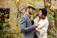 A young retro couple. Gangster guy is smoking a cigar, and the girl is looking at him in love. Outdoors. A young and enamored retro couple are standing in the Stock Image