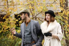A young gangster retro couple walking holding hands. The guy is smoking a cigar, and girl is watching to him. Retro. A young and enamored retro couple walking stock photo