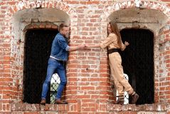 Young enamoured pair a brick wall Royalty Free Stock Images