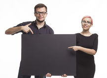 Young encouraged couple showing presentation pointing placard Royalty Free Stock Photography