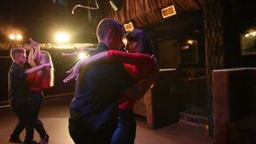 Young energetic attractive couples dancing salsa, bachata, latin dance on open air party in evening time