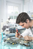 Young energetic male tech or engineer repairs electronic equipme Stock Photography