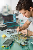 Young energetic male tech or engineer repairs electronic equipme Royalty Free Stock Images