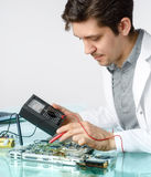Young energetic male tech or engineer repairs electronic equipme Royalty Free Stock Image