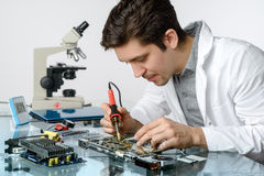 Young energetic male tech or engineer repairs electronic equipme. Nt in research facility. Shallow DOF, focus on the face and hands of the worker Royalty Free Stock Photo