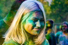 Young energetic teenagers at the festival of paints of holi in Russia. Having fun outdoors. Multicolored powder colors the face. Closeup portrait stock image