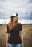 Young energy happy woman in hip-hop cap looking to camera on yellow field with power pylons Royalty Free Stock Images