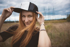Young energy happy woman wears a cap hip-hop  on yellow field with power pylons, close up Stock Photos