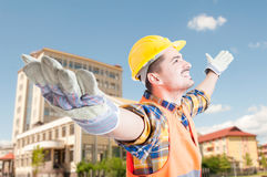 Young engineer or architect standing with arms outstretched Stock Images