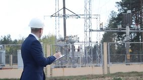 A young engineer in the background of a power plant writes data to a tablet. Inspector stock video footage