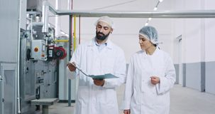 Young engineer and baker woman in a big bakery industry factory have a conversation looking through the plan and. Analyzing something. 4k stock video footage