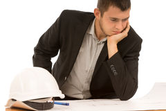 Young engineer, builder or architect. Sitting with his chin resting on his hand puzzling over a blueprint, on white stock photos