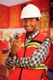 Young engineer carpenter wearing helmet, square pattern flanel shirt with red safety vest, holding small handheld Stock Image