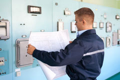 Young engineer at control room. Young engineer looking at blueprints at control room Stock Image