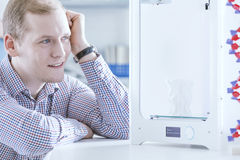 Young engineer with 3D printer. Young engineer sitting at office with 3D printer Stock Photography