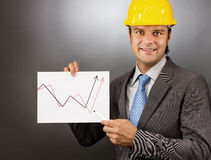 Young engineer drawing a rising graph, representing business gro Stock Images