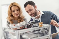 Young engineer explaining principles of 3D printer work. Clear explanation. Pleasant bristled young engineer explaining the principles of 3D printers work to his royalty free stock photography
