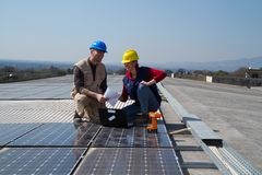 Young engineer girl and skilled worker on a roof. Young engineer girl and an elderly skilled worker fitting a photo voltaic plant Royalty Free Stock Image