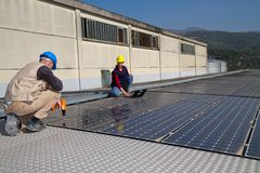 Young engineer girl and skilled worker on a roof. Young engineer girl and an elderly skilled worker fitting a photovoltaic plant Stock Photo