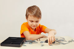 Young engineer is going to play with mechanical constructor at table Stock Image