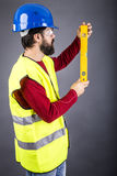 Young engineer with hardhat and reflective vest holding a levele Stock Photos