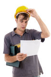 Young engineer with hardhat. Shocked while reading a construction plan Stock Photography