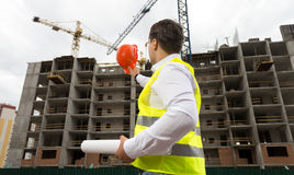 Young engineer holding blueprints and pointing at building site. Rear view of young engineer holding blueprints and pointing at building site with hardhat Stock Photo