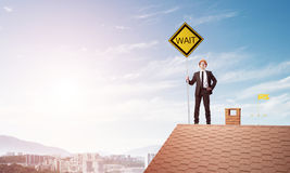 Young engineer on house brick roof holding yellow signboard and looking at city. Mixed media Royalty Free Stock Images
