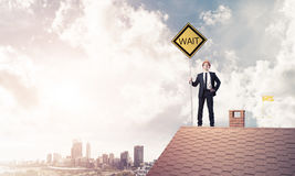 Young engineer on house brick roof holding yellow signboard and Royalty Free Stock Photo