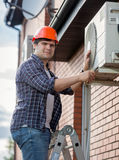 Young engineer installing air conditioner on building outer wall. Portrait of young engineer installing air conditioner on building outer wall stock photo