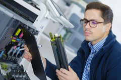 Young engineer in lab adjusting 3d printers components Royalty Free Stock Photos