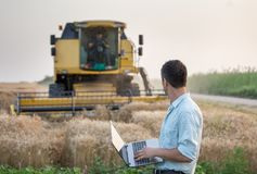 Engineer with laptop and combine harvester Stock Image