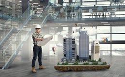 Young engineer man. Mixed media. Builder man interior and his construction exterior model. Mixed media Royalty Free Stock Photos