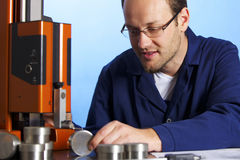 Young engineer measuring. Young male engineer in blue overall taking precision measurement of metal parts with micrometer, isolated on blue background Stock Images
