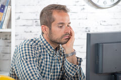 A young engineer pensive at his computer Stock Images
