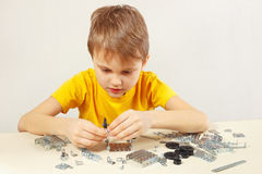 Young engineer plays with mechanical starter kit at table Stock Photos