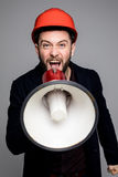 Young engineer is shouting out over megaphone against grey background. Royalty Free Stock Photo