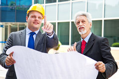Young engineer showing something to his partner at building site Royalty Free Stock Image