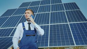 Young engineer speaks on the phone on the background of large solar panels stock photography