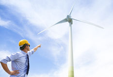 Young engineer standing and point to wind generator Royalty Free Stock Images