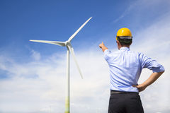 Young engineer standing and point to wind generator Royalty Free Stock Photos