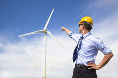Young engineer standing and point to wind generator Stock Photo
