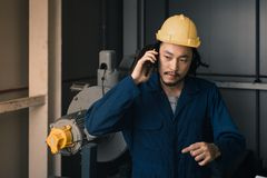 Young engineer talk to his cellphone in factory royalty free stock image