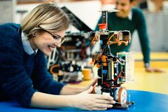 Young engineer testing her robot in workshop. Young beautiful engineer testing her robot in workshop royalty free stock images