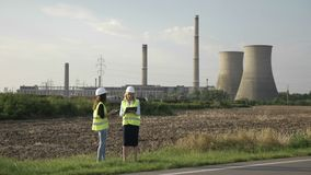 Young engineer women with helmet holding map and using tablet pc discussing about energy power plant supervising industrial area -. Young engineer women with stock footage