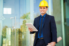 Young engineer at a work site. Portrait of a good-looking young engineer in a suit and helmet using a tablet computer at a construction site Royalty Free Stock Photos