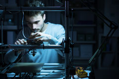 Young engineer working on a 3D printer. Young engineer working at night in the lab, he is adjusting a 3D printer's components, technology and engineering concept royalty free stock photos