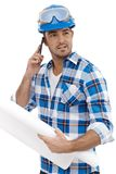 Young engineer working in hardhat. Talking on mobile phone stock photo